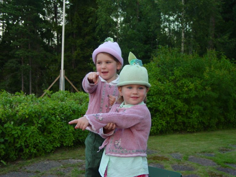 Two girls playing in the yard, wearing matching sweaters and Margareta Horn Design hats.