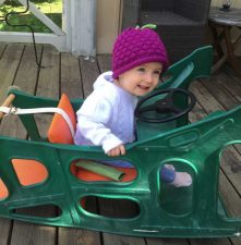 Girl in toy rocker wearing Beauty Berry Hat by Margareta Horn Design