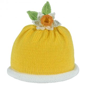 Yellow knit hat wil white roll brim decorated a daffodil and two green knit leaves