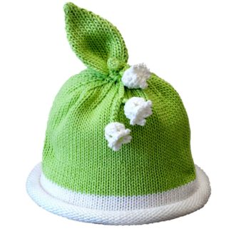 Green knit hat with white rolled brim topped with cluster of white knit lily flowers and green knit leaf