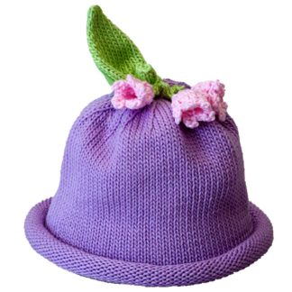 Lavender knit hat with rolled brim crowned with three pink knit linnea flowers and a green knit leaf.