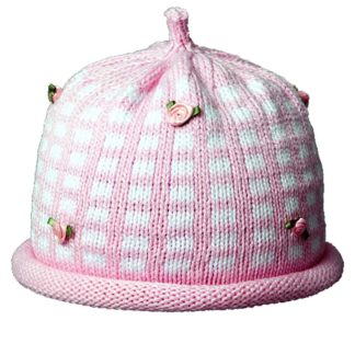Knit hat pink with white checks in mosaic pattern. The cap crown and rolled brim are pink and the hat is accented with pink silk miniature roses