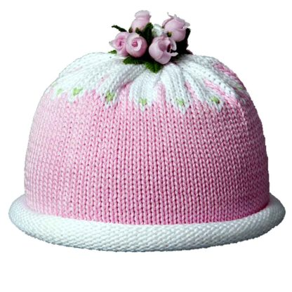 Pink knit hat with white rolled brim and crown. The cap is topped with a ring of miniature pink silk rose buds