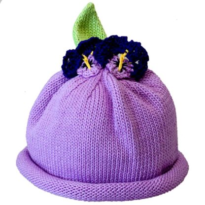 Lavender knit hat with rolled brim topped with two knit purple pansy flowers and a knit green leaf