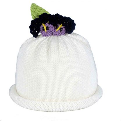White knit hat with two colored purple pansies and a green knit leaf. The hat has a white roll brim.