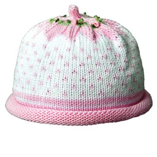White knit hat with pink snowflake stitches. The rolled brim and crown of the cap is pink. The crown is decorated with miniature silk rosebuds