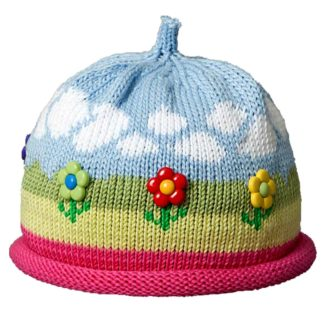 Knit hat outdoor design with clouds in the sky, flowers in the grass and hot pink rolled brim. The flowers are flower shaped buttons.