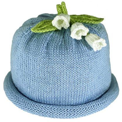 Blue knit hat decorated white lilies and green knit leaves