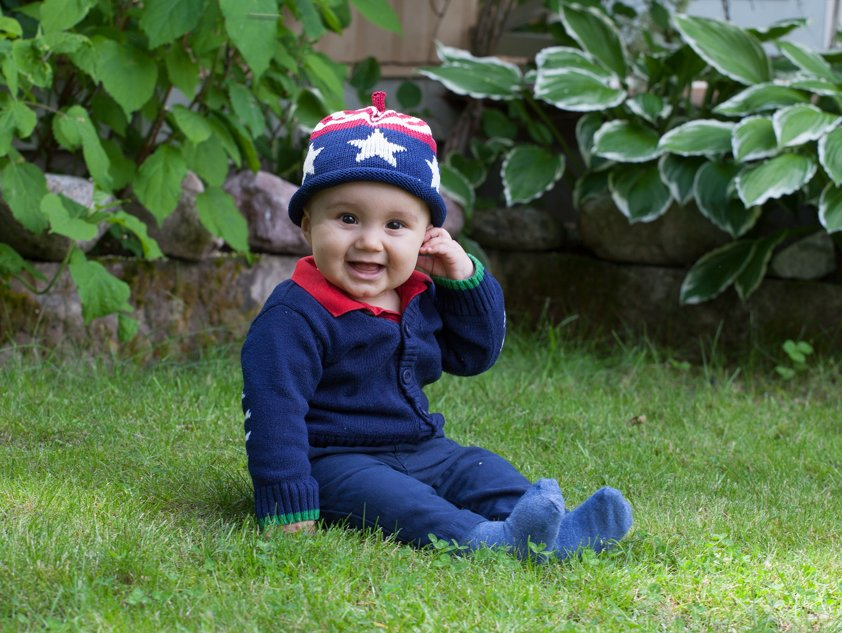 Baby Boy sitting in grass wearing the Old Glory Knit Hat stars and stripes red white and blue