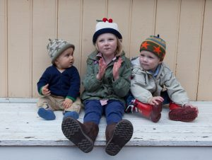three children sitting together each wearing a Margareta Horn Design hat. The girl is wearing a cherry hat and the boys are vearing sttar hats