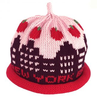 "knit hat decorated with black skyline of tall buildings with baby pink ""sky"" and a ring of apples"